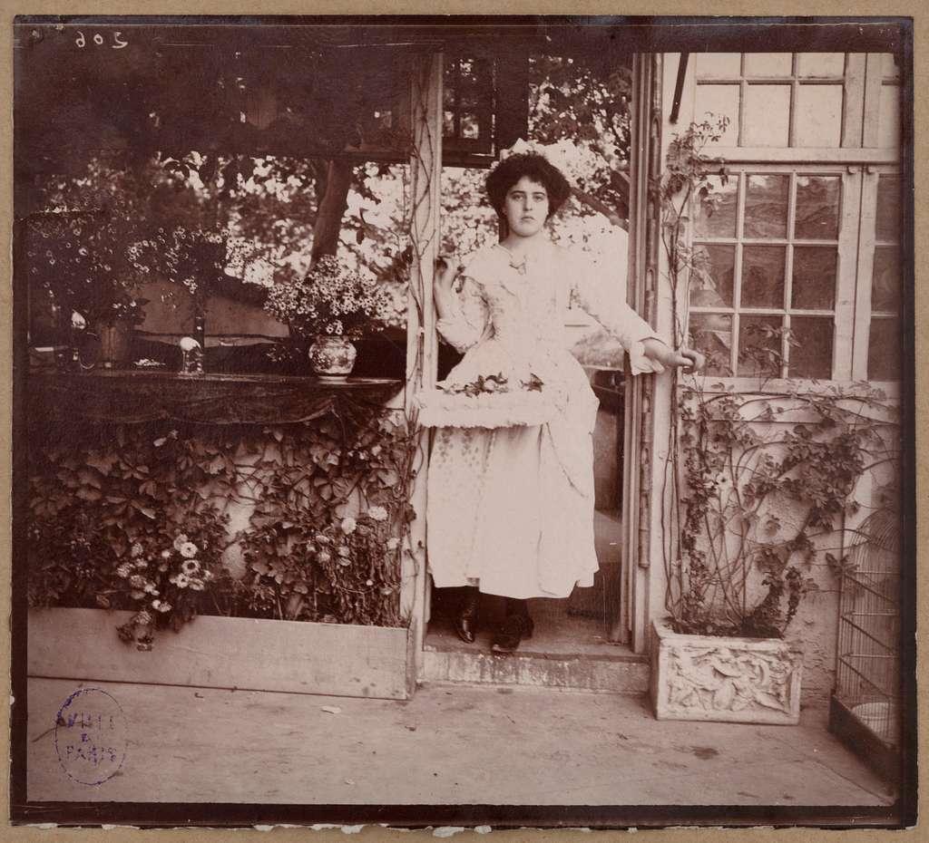 Femme en costume dans l'embrasure d'une porte, Exposition universelle de 1900, Champs de Mars, 7e arrondissement, Paris.